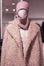 A Mannequin In A Shop Window In A Winter Coat Made Of Faux Fur And A Balaclava Hat On His Head. Fashionable Concept Of Autumn Clothes For Women