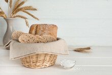 Cut Delicious Ciabatta In Wicker Basket And On Beige Wooden Table, Space For Text