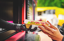 Chef Hands Gives A Hot Dog To Man From Food Truck On Street
