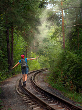 Summer Staycation. Tourist With Backpack Walks Alone On Railway Through The Enigmatic Forest. Woman Hiker Waves Her Arms And Balancing On The Rail, Back View, Vertical Photo, Selective Focus.