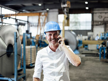 Smiling Male Engineer Talking On Mobile Phone At Metal Industry