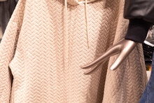 Trendy Quilted Jumper Of Beige Color In The Window Of A Women's Clothing Store. Hand Mannequin On The Background Of Hangers With Upper Seasonal Clothing For Autumn And Winter