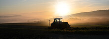 Tractor Ploughing The Field At Sunrise In Late Summer Or Autumn.