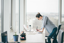 Concentrated Young Businesswoman With Glasses Writes In Paper Notebook Looking At Display Of Contemporary Laptop Near Panoramic Window In Company Office.