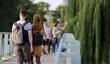 Para młodych ludzie, kobieta i mężczyzna z plecakami spaceruje po moście we Wrocławiu.