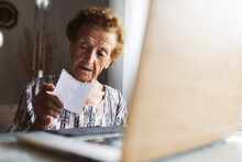 Senior Woman Reading Letter While Sitting With Laptop At Home