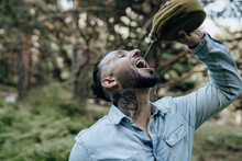 Thirsty Bearded Male Hipster Drinking Water From Bottle In Forest