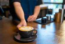 Asian Man Barista Making Hot Coffee Latte In Coffee Cup To Customer On Bar Counter At Cafe. Male Coffee Shop Waiter Serving Hot Coffee With Milk To Client. Small Business Restaurant Owner Concept.
