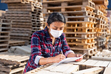 Woman Manager In Protective Mask Keeps Records Of Building Materials In The Open Area Of A Construction Store