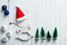 Santa Hat, Rocking Horse And Christmas Tree Ornaments On White Wooden