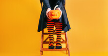 A Little Girl Dressed In A Witch Costume For Halloween Holds A Pumpkin Close-up Against The Background Of Her Legs. A Child Holds Jack's Pumpkin For Halloween.