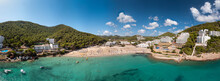 Large Format Wide Angle Panoramic Aerial Photo Of The Spanish Island Of Ibiza Showing The Beautiful Beach Front And Holiday Hotels At The Beach Of Cala Llonga In The Summer Time, On A Sunny Day