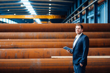 Businessman With Digital Tablet Standing At Steel Pipe Warehouse