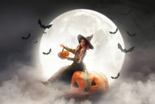 A Little Girl In A Witch Costume Sits On A Pumpkin Against The Background Of The Moon, Bats Fly On Halloween Holiday Party In Smoke