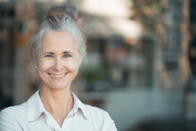 Smiling Woman With Gray Hair Bun In Cafe
