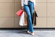 Young Woman Holding Shopping Bags While Standing On Footpath