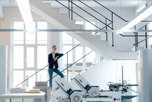 Female Business Professional Leaning On Railing In Workshop