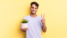 Hispanic Handsome Man Smiling And Looking Friendly, Showing Number Two. Decorative Plant Concept