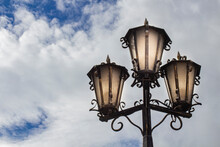 Street Lamps Made Of Metal Against The Background Of The Evening Sky With Beautiful Clouds, Copy Space.
