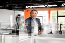 Mature Businessman Standing At Desk
