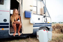 Young Woman Holding Smart Phone While Sitting At Doorway Of Camping Van