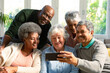 Five happy diverse senior friends sitting on sofa and looking at smartphone