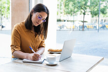Businesswoman Writing In Diary While Working At Coffee Shop