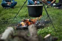 Dark Big Pot Or Cauldron, Cooking Pan With Boiling Water Inside Above The Fire Somewhere In The Park Or Mountains, Camping Concept