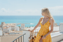 Woman In Dress Standing On Balcony And Enjoying Seascape