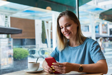 Female Blond Freelancer Using Mobile Phone In Coffee Shop