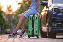 Closeup Of Young Woman Slim Legs Resting On Suitcase Bag Beside Car. Travelling And Vacations Concept.