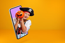 Little Girl In A Carnival Costume Of A Pirate On Halloween Looks From A Smartphone. The Child Is Online On The Screen Of A Mobile Phone And Holds A Bucket With A Pumpkin Lantern. Copy Space.