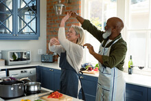 Happy Senior Diverse Couple In Kitchen Wearing Aprons, Cooking Together, Dancing