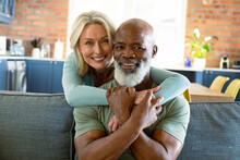 Portrait Of Happy Senior Diverse Couple In Living Room Sitting On Sofa, Embracing And Smiling