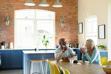Happy Senior Diverse Couple In Kitchen Sitting At Table, Drinking Coffee