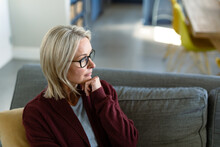 Thoughtful Senior Caucasian Woman In Living Room Sitting On Sofa, Thinking