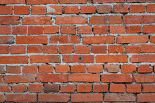 Photo Of The Texture Of A Brick Wall, Made Of Red Clay Bricks With Inflows Of Cement Mortar And Uneven Brickwork.