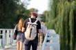 Młody mężczyzna z plecakiem i słuchawkami na uszach, idzie po moście we Wrocławiu.