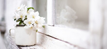 Still Life With Mug With Flowering Branch Of Apple Tree On White Window Sill Near An Old Wooden Window. Vintage Image. Spring Background.