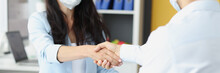 Young Business People In Medical Masks Shake Hands At Work Table