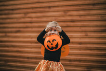 Cute Little Girl Wearing Witch Costume Holding Pumpkin Bucket With Candies On Halloween. Trick Or Treat.