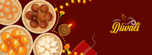 Top View Of Presenting Indian Sweets With Lit Oil Lamp (Diya), Firecracker Stripe And Lighting Garland On Red Background For Happy Diwali Celebration.