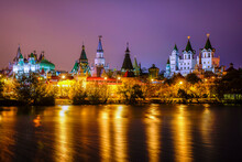 Panorama Izmailovo Kremlin Buildings With Turrets Are Illuminated By Evening Illumination Against The Background Of A Beautiful Evening Lilac Embankment, On The Banks Of The Reservoir The River.