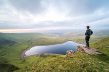 Man Standing On Rocks Overlooking Llyn Y Fan Fach Lake. Brecon Beacons National Park. Black Mountain, Carmarthenshire, South Wales, The United Kingdom. Hiking In The UK Concept.