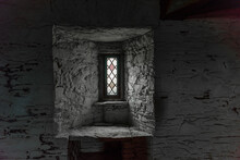Narrow Glazed Glass Window In The Stone Wall Of A Castle.