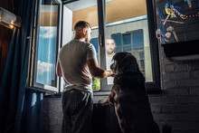 Dog And Man Looking Through Window At Home