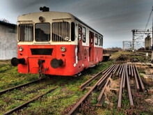 Retro Train Wagon Of Red Color. Vintage Locomotive Made In Yugoslavia. Sremska Mitrovica, Serbia. The Metal Body Of A Railway Vehicle. Rusty Rails. Railroad Station. Empty Carriage At A Dead End