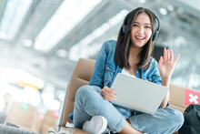Attractive Asian Female Traveller Wear Casula Cloth Headphone Using Laptop For Wating Flight Departure At Airport Terminal,asian Female Smile Hand Waving Greeting Looking At Camera Travel Idea Concept