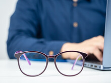 Close Up Glasses On The Table With Man Working With Laptop Behide