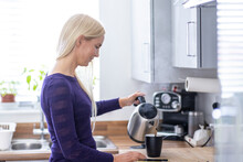 Woman Pouring Hot Water In Mug While Preparing Coffee In Kitchen At Home